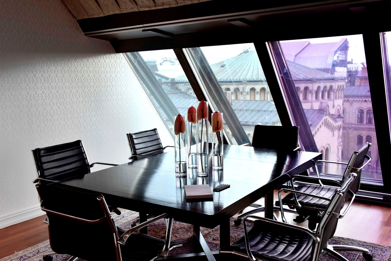 The meeting room has exclusive office chairs and a round table with a view of the Parliament.