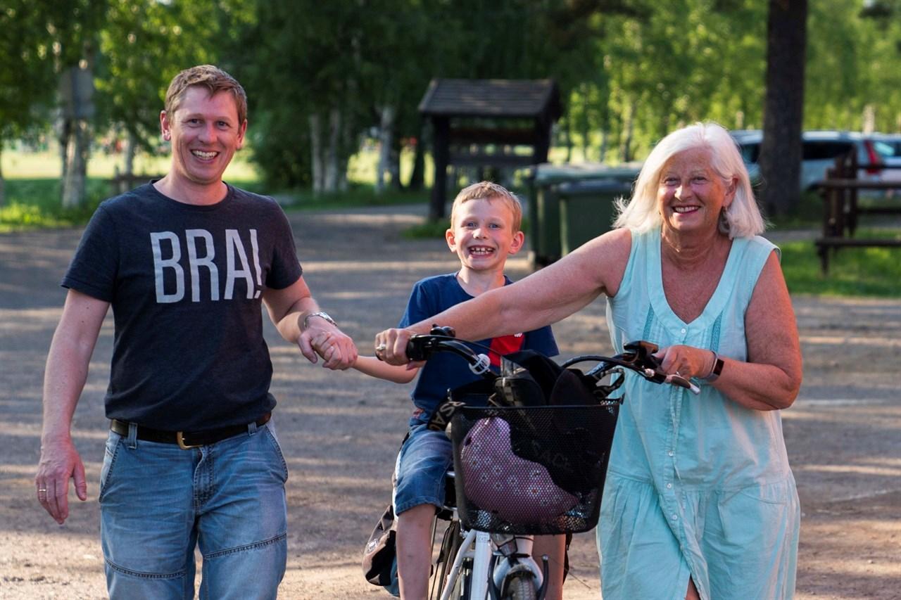 TREGENERASJONERPÅTUR: Noah Nybråten Buskerud (8) tar med seg farmor Sissel Buskerud og pappa Anders Nybråten Buskerud innom Sørum Gård i pausen på fotballkampen til broren Leo.